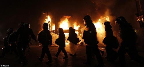 克斯顿/骚乱中防暴警察在布里克斯顿高街把守。在暴力事件发生后,戴着...